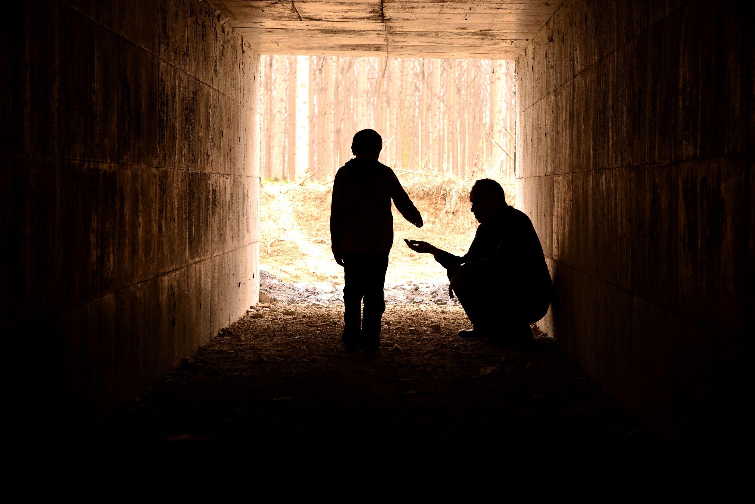 Silhueta de uma criança dando uma moeda para um homem que esta agachado, ambos embaixo de um túnel