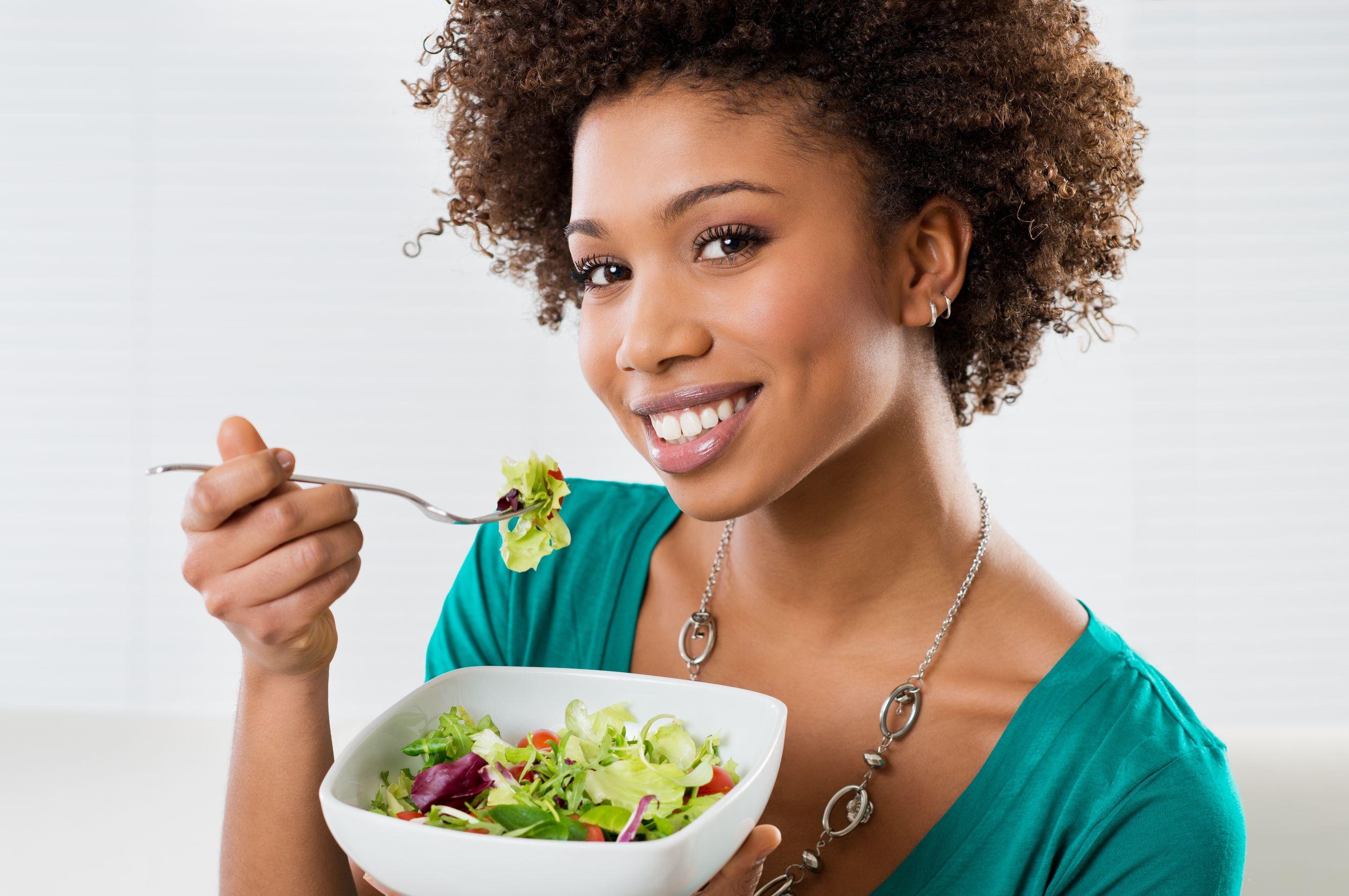 Mulher negra comendo uma salada na sala de casa.