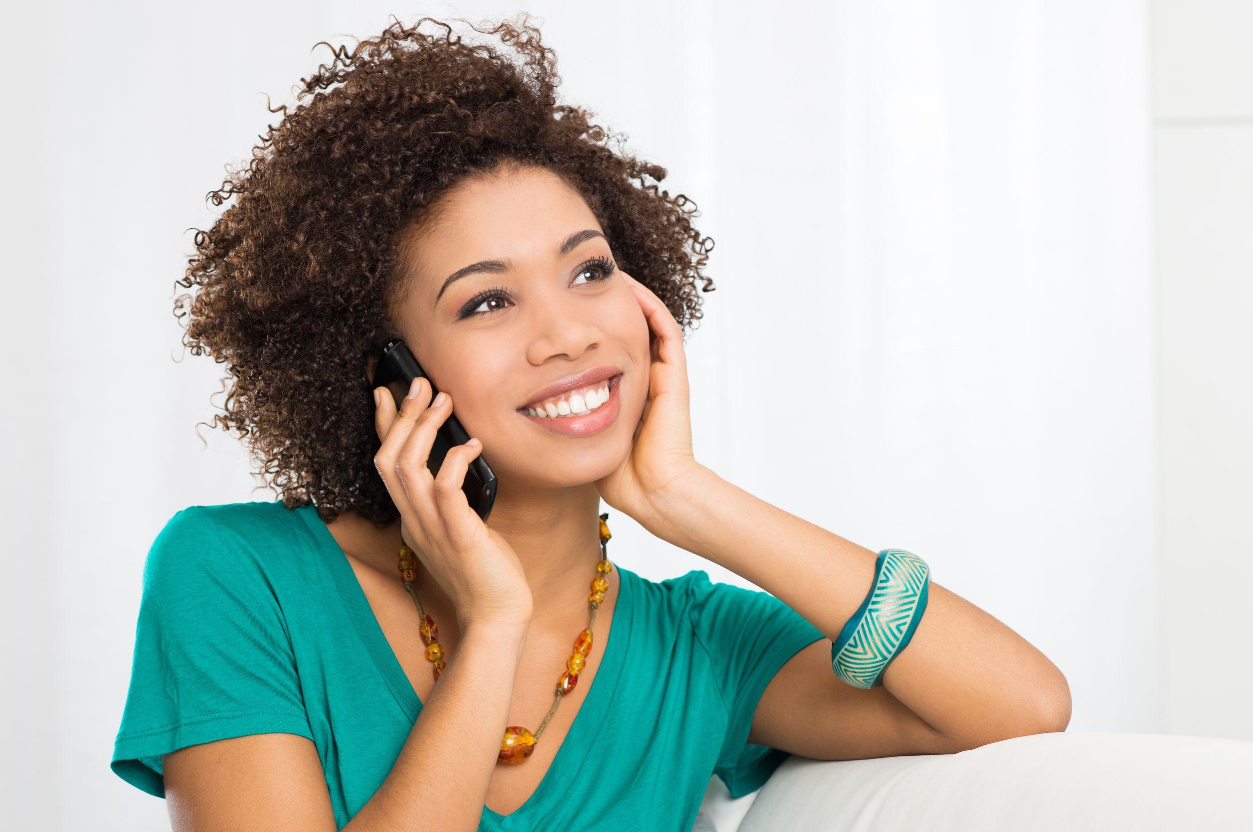 Mulher negra jovem e sorridente sentada em sofá branco enquanto fala no telefone.
