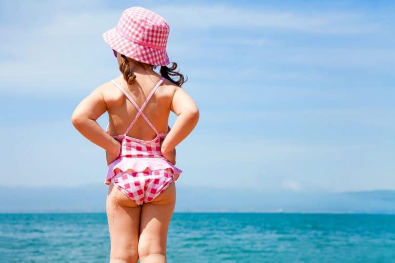 menina em um maiô olha para o mar
