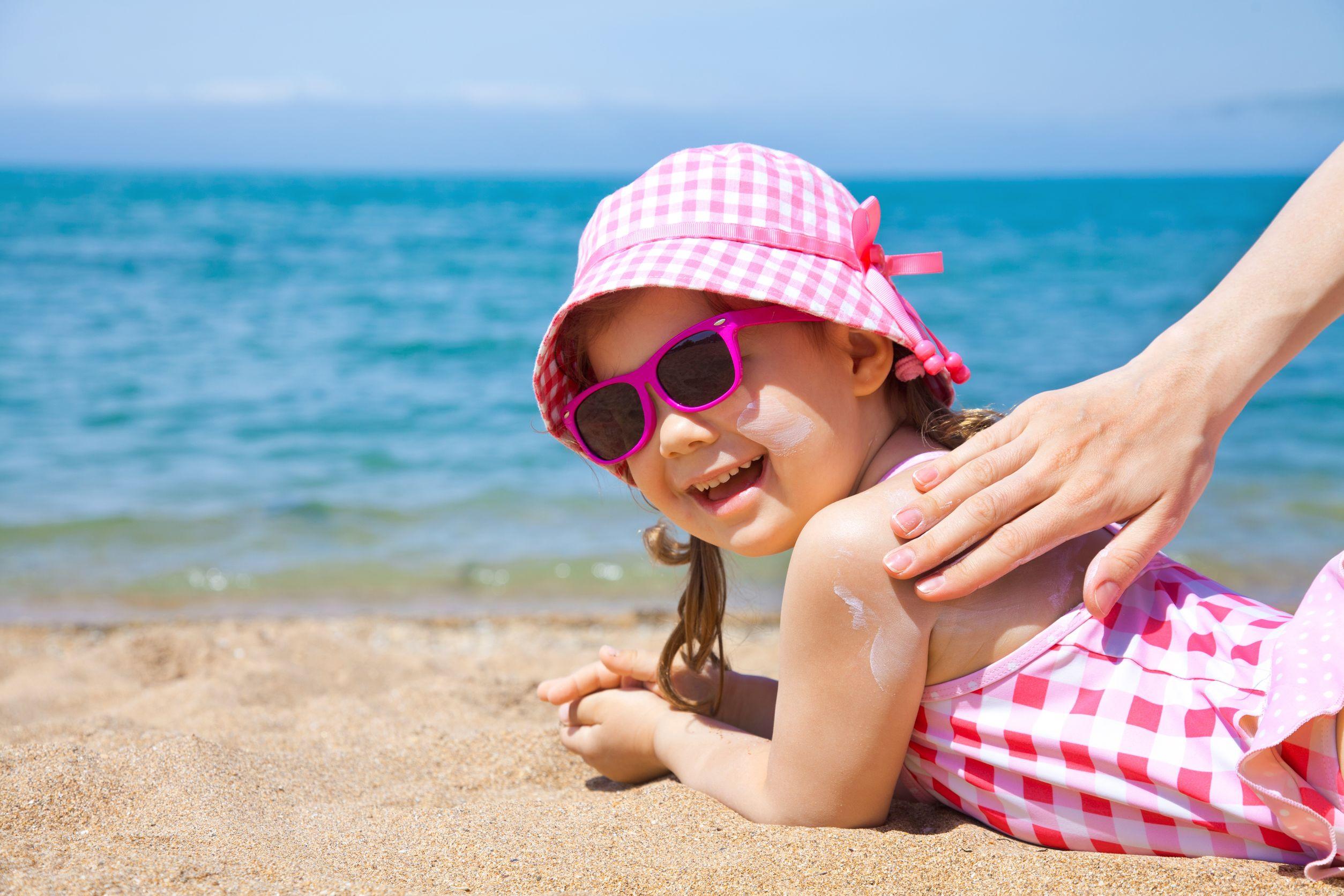 Menina pequena vestida com um maio rosa, óculos de sol e chapéu de praia, a beira mar, com a mão de um adulto passando protetor nas suas costas.