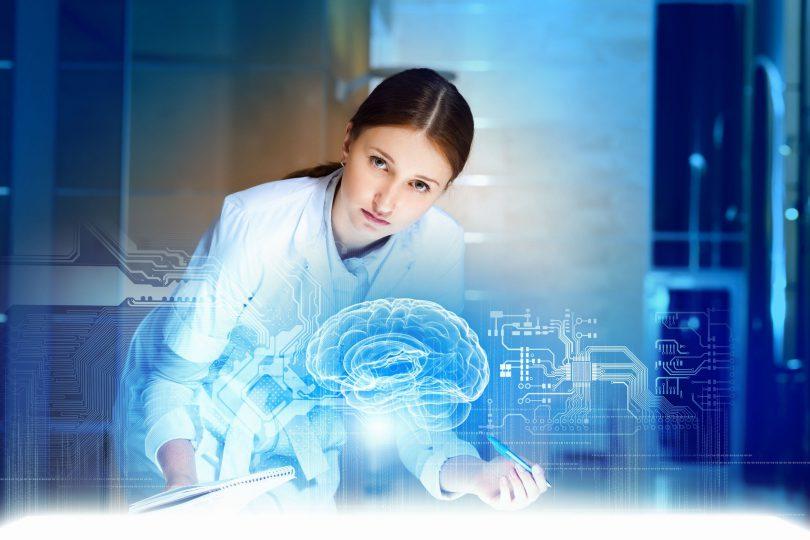 Jovem mulher vestida de médica analisando a projeção eletrônica de um cérebro humano.