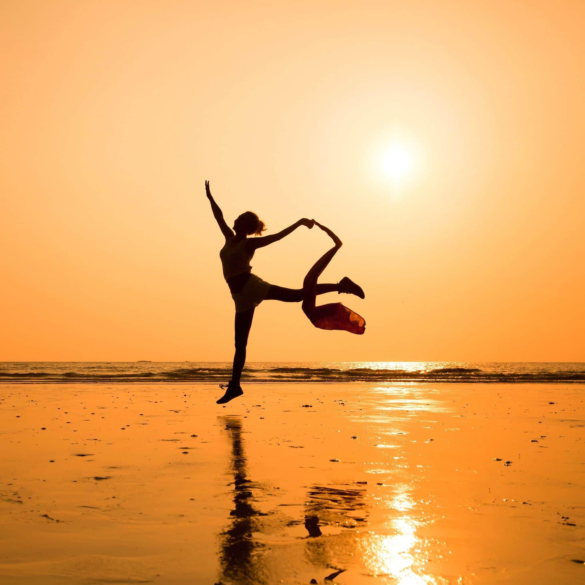 Silhueta de mulher dançando na praia.