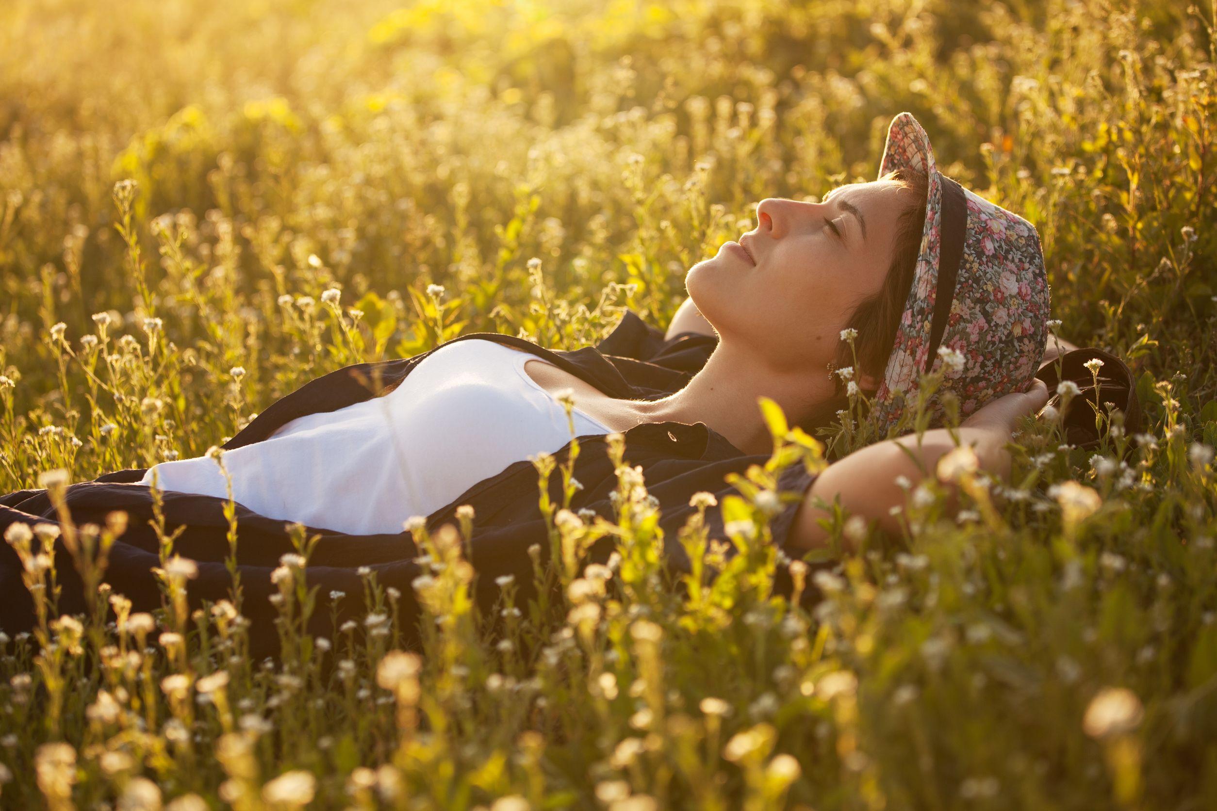Garota usando chapéu e camisa xadrez deitada em campo de flores amarelas durante o pôr-do-sol.