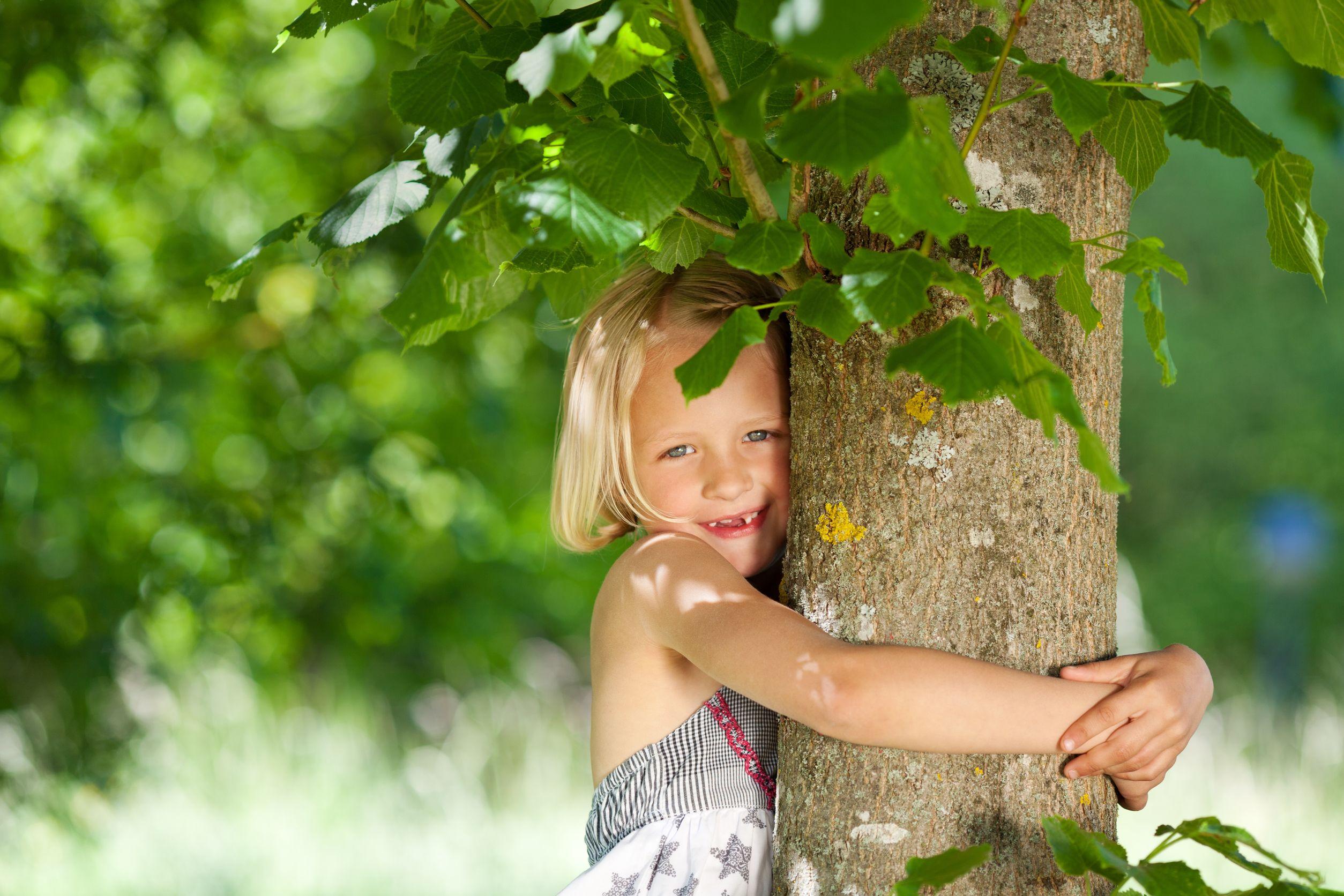 Menina abraçando um tronco de árvore.