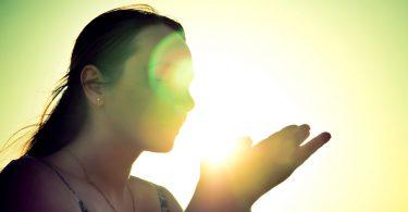 Silhueta de uma mulher segurando raios de sol.