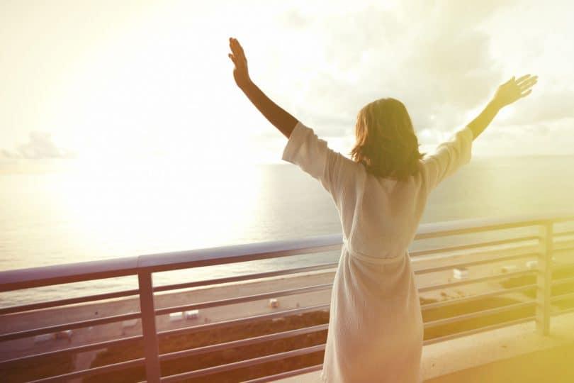 Mulher feliz com as mãos para cima olhando para o oceano.