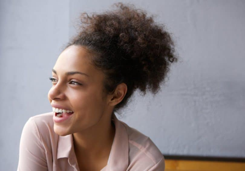 Mulher negra com cabelo preso sorri e olha para o lado