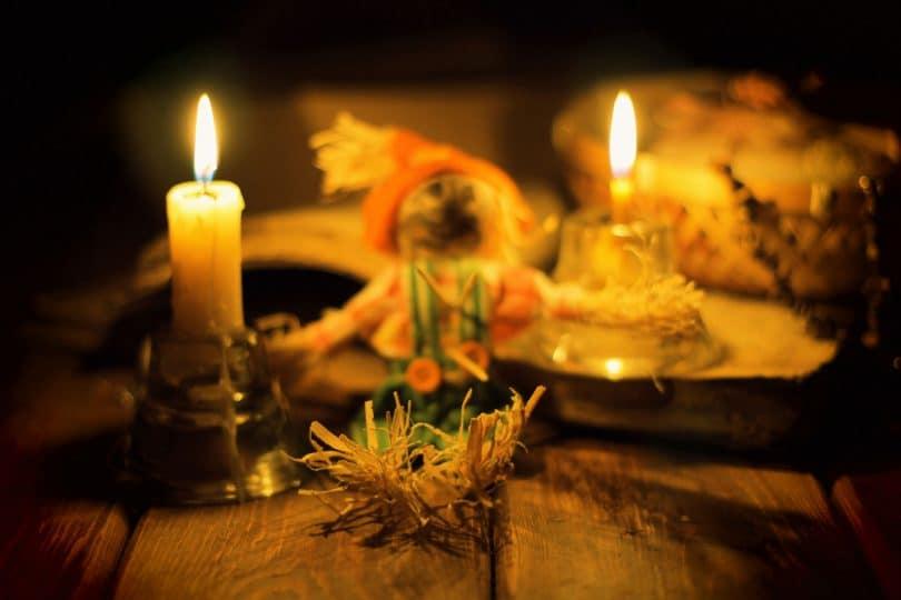 Velas, incensos e palhas colocados em cima de mesa de madeira.