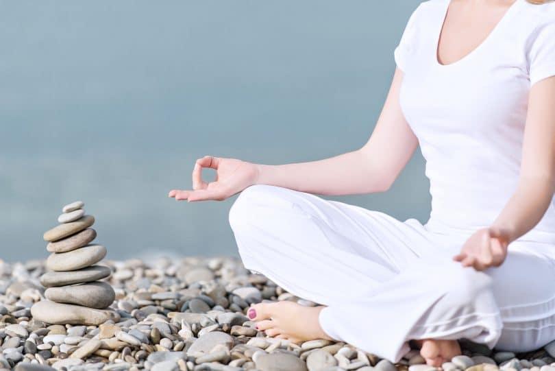 mão de uma mulher meditando em uma pose de ioga na praia