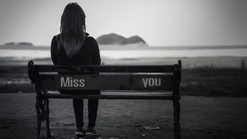"""Mulher sentada em um banco em frente ao mar. No banco estão escritas as palavras """"Miss"""" onde ela está sentada e """"You"""" na ponta oposta do banco. """"Miss You"""" é traduzido como """"Sinto sua falta"""" em português."""