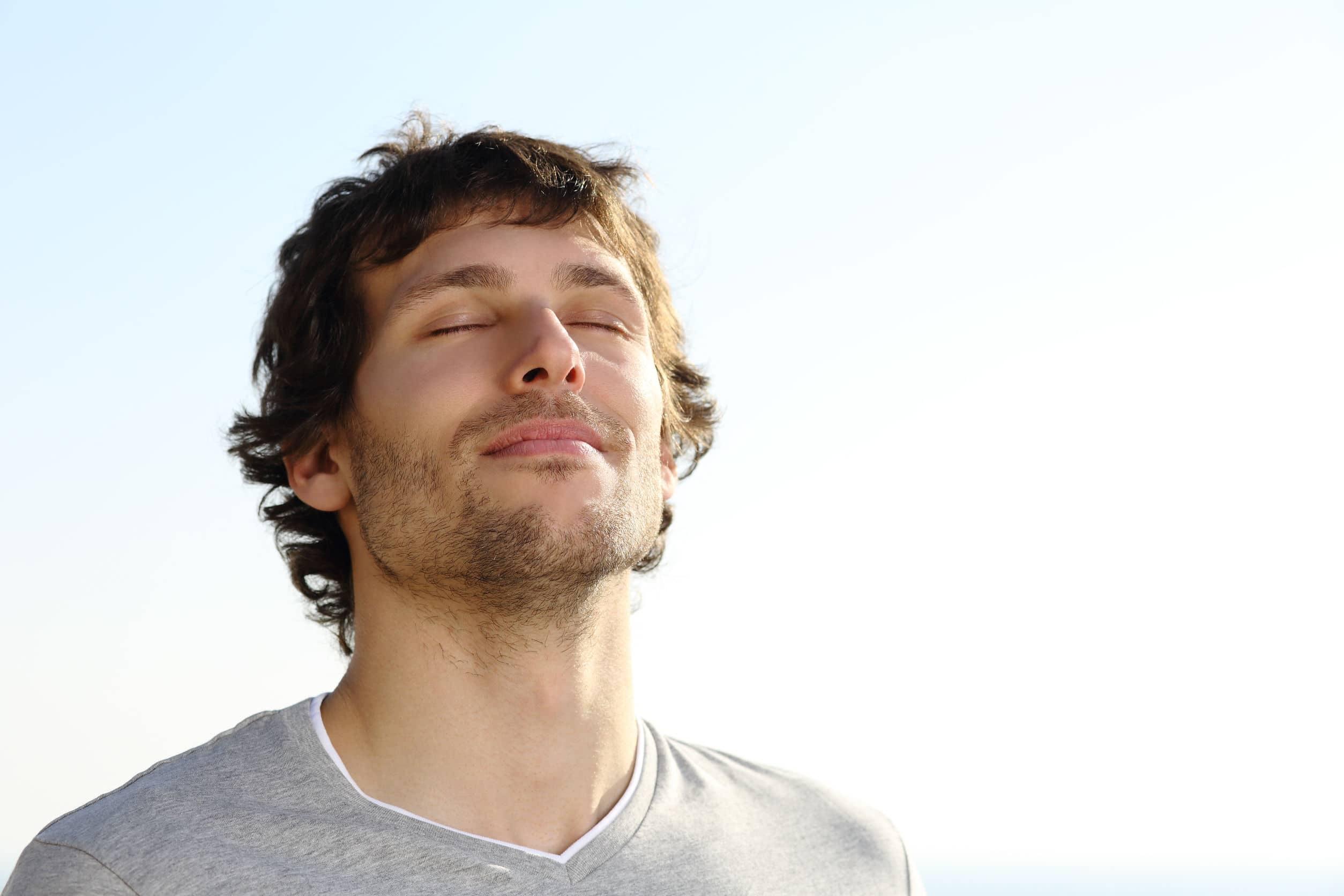 Homem jovem de olhos fechados respirando ao ar livre com o céu ao fundo