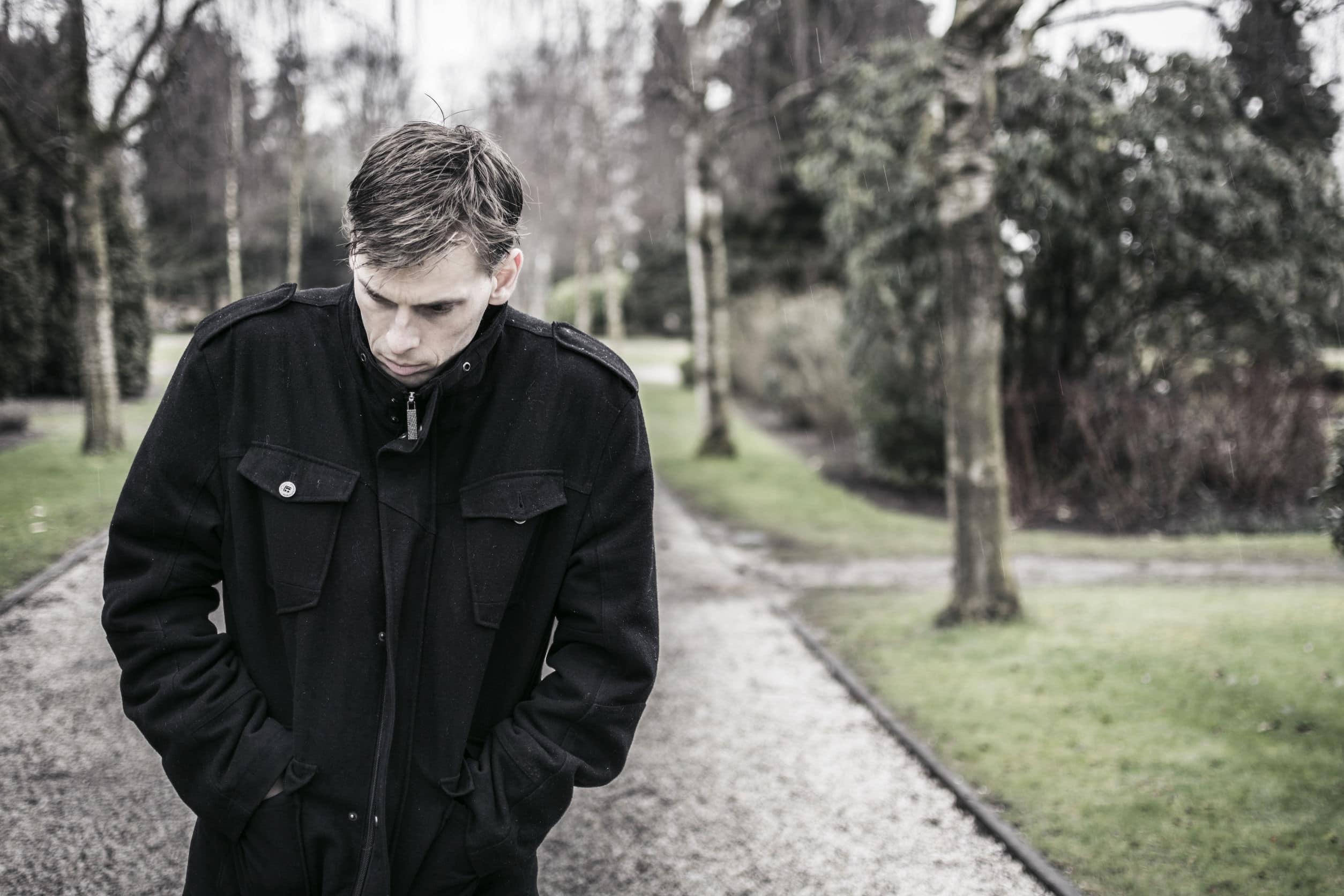 Homem deprimido andando nas ruas de um parque. Ele usa um sobretudo preto.