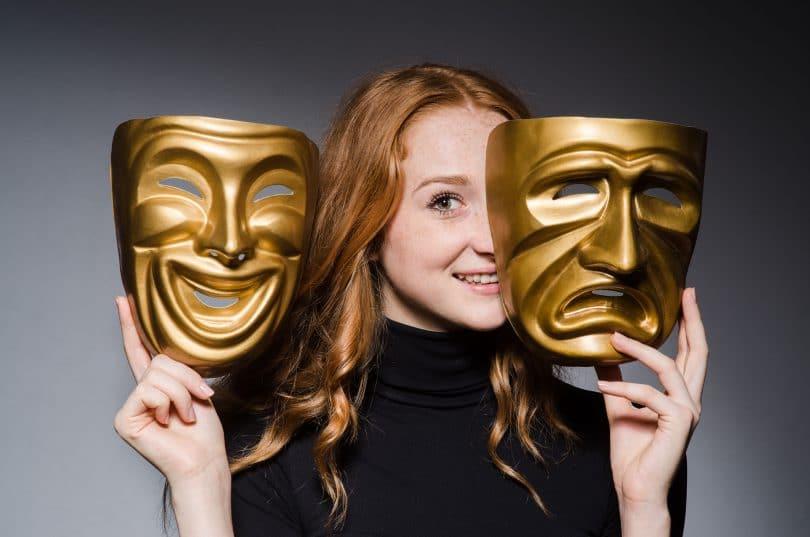 Mulher ruiva segurando as máscaras características da alegria e da tristeza.