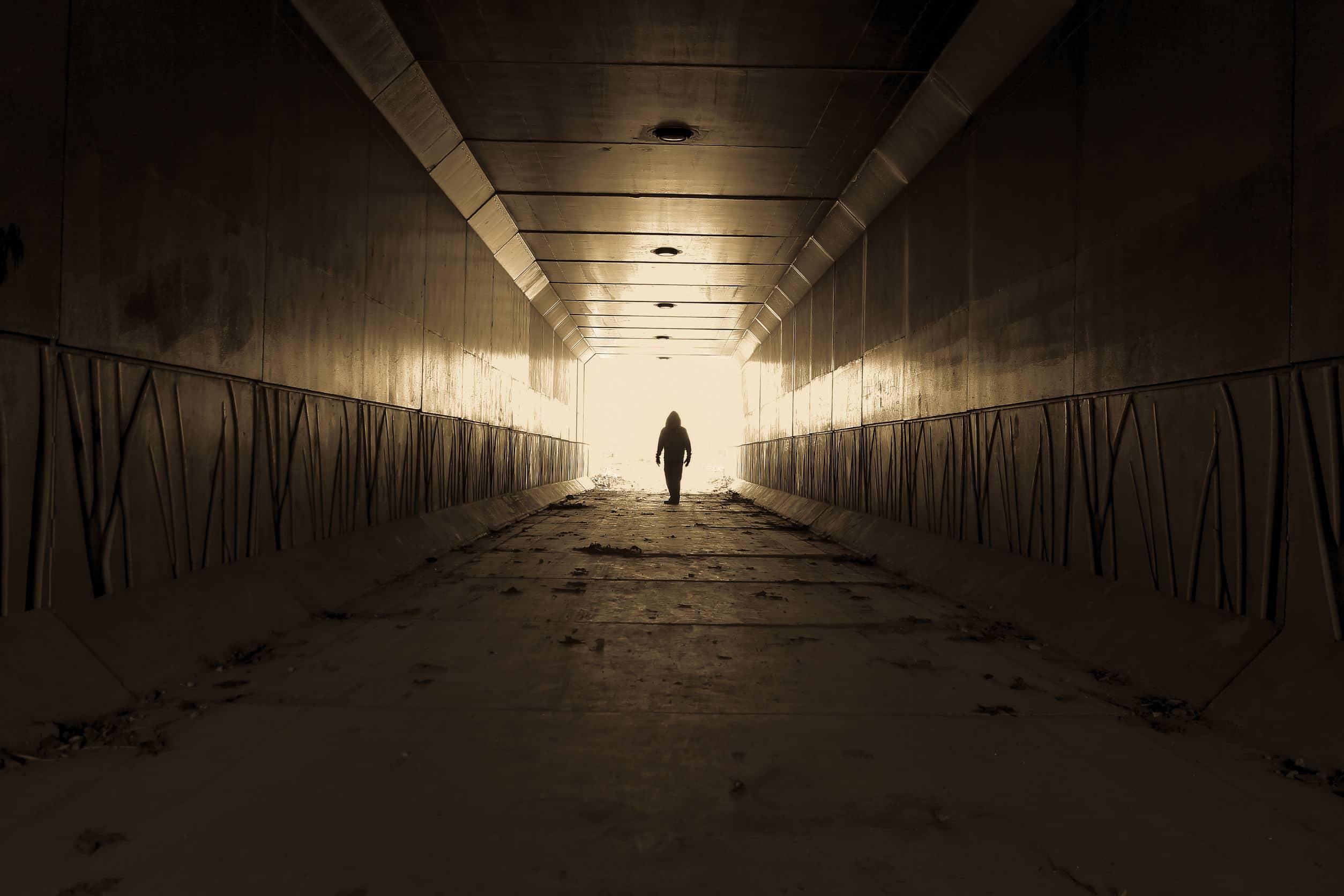 Silhueta de homem vestindo um capuz, em túnel com uma luz no final