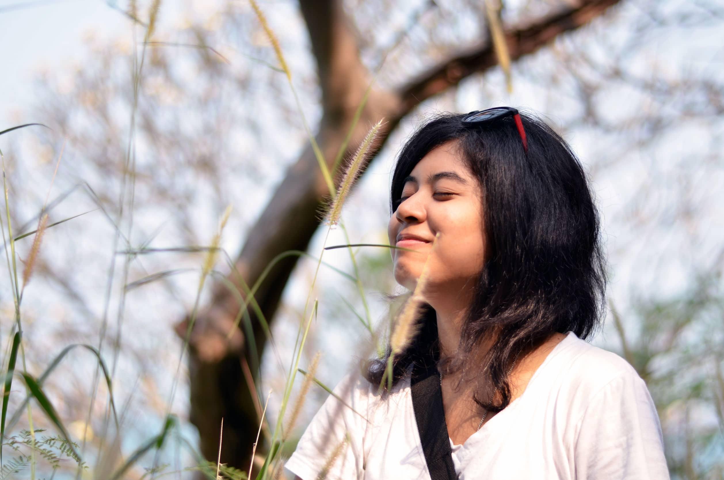 Mulher asiática nova respirando ar fresco no jardim