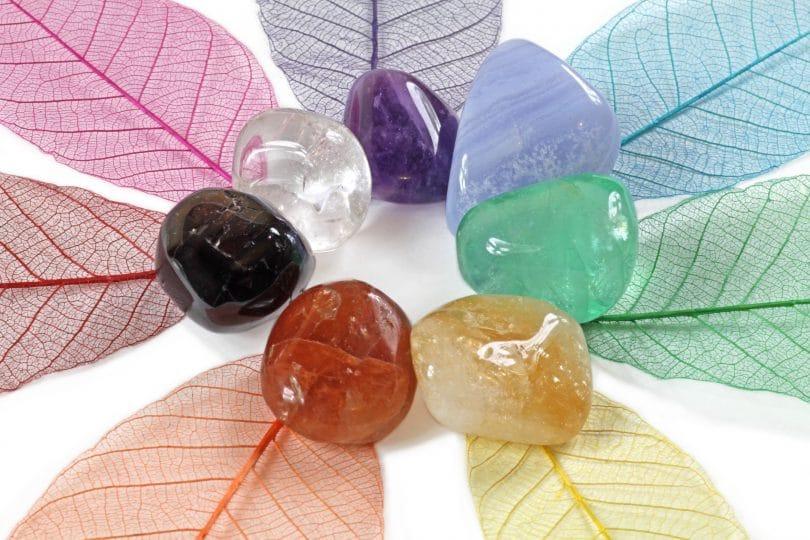 Cinco pedras dos chakras em circulo, cada uma com uma cor diferente. São elas marrom, amarelo, verde, lilás, roxo, transparente e preto.