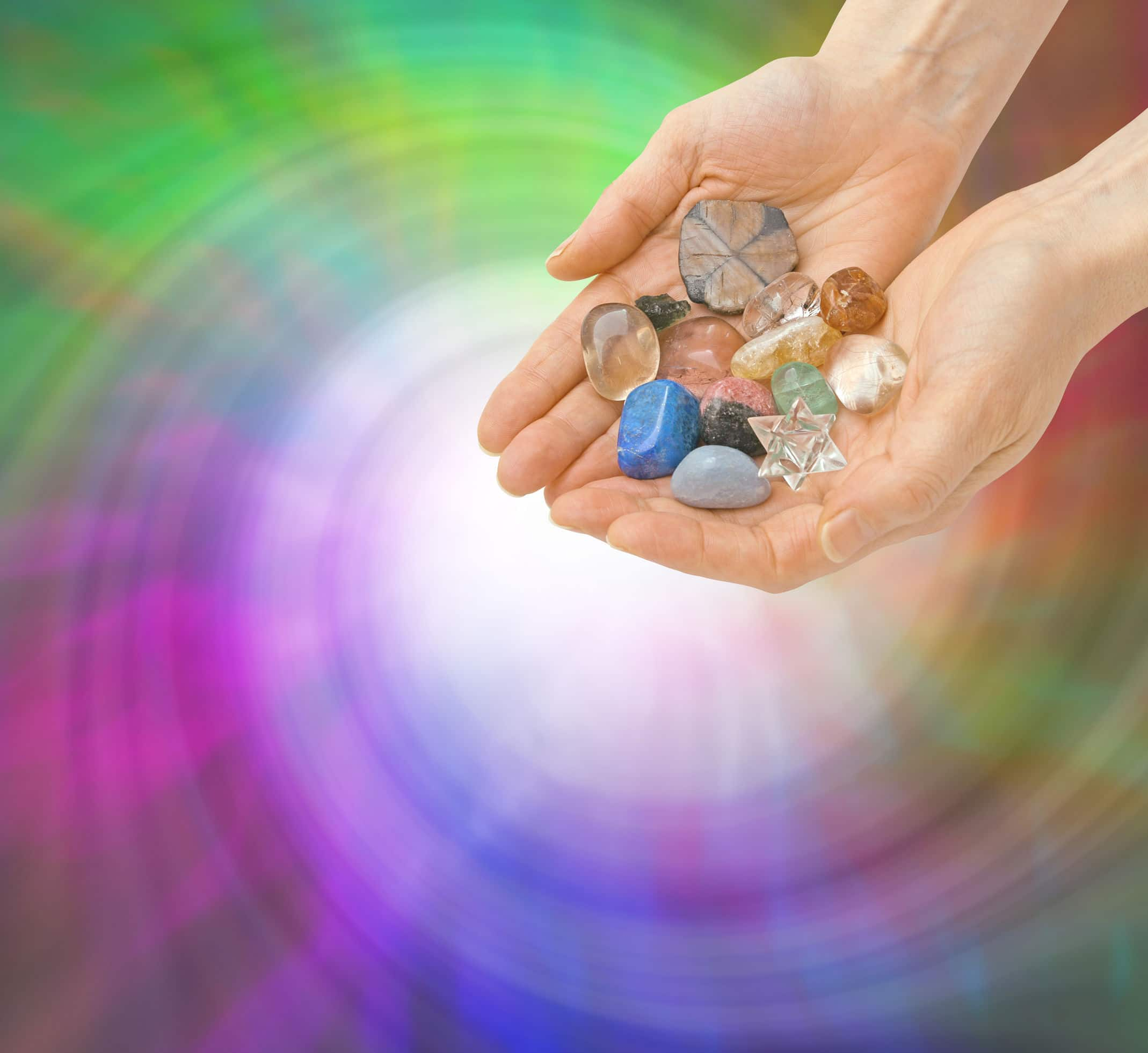 Imagem com duas mãos segurando diversas pedras e cristais coloridos, na frente de um fundo colorido em espiral.