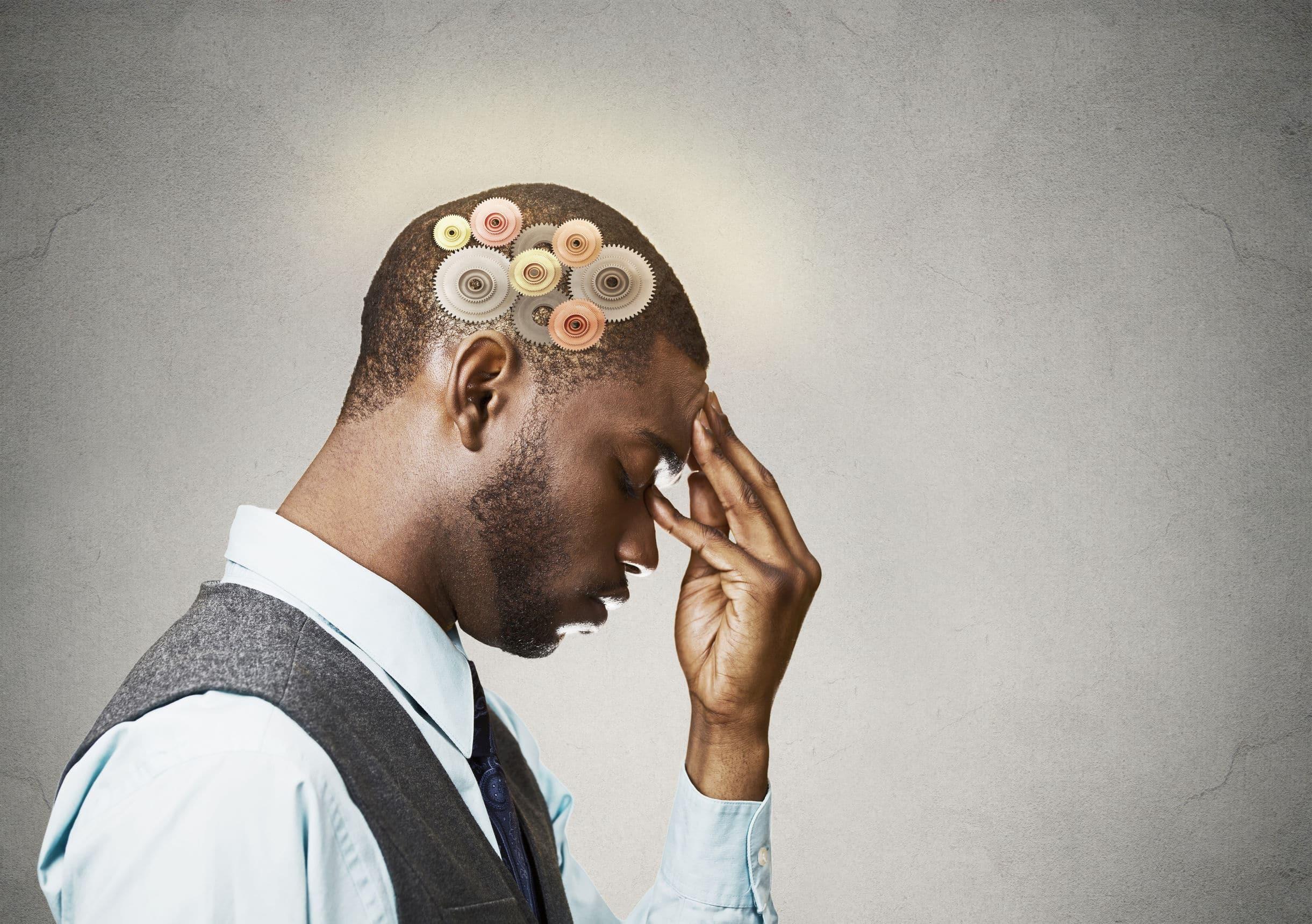 Foto de homem negro pensativo apoiando o rosto na mão de olhos fechados, com desenho de engrenagens na sua cabeça