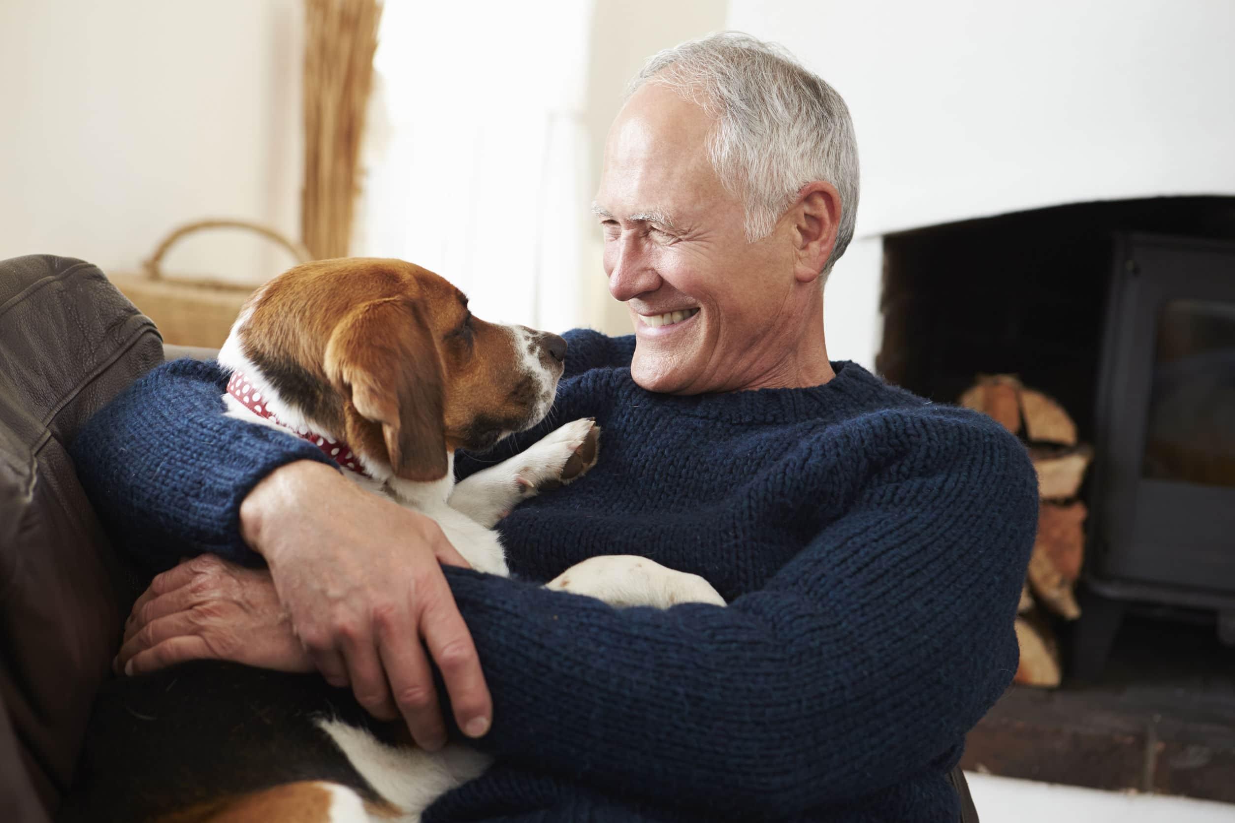 Homem idoso sorridente sentado em um sofá abraçado ao seu cachorro.