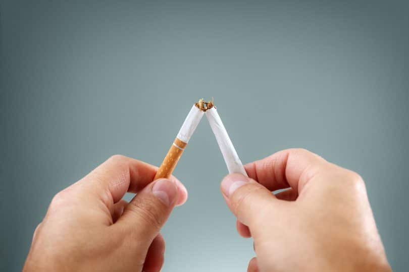 Quebrando um cigarro no meio. Conceito para parar de fumar