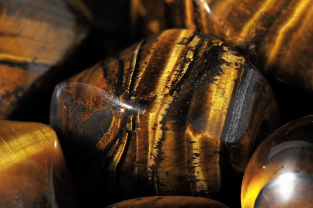 Uma pedra com mesclas de preto laranja e marrom como listras de tigre ao lado de outras similares. A pedra é conhecida como Olho de Tigre.
