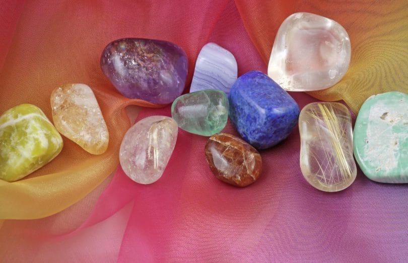 Fotos de pedras e cristais coloridos colocados em cima de uma mesa colorida.
