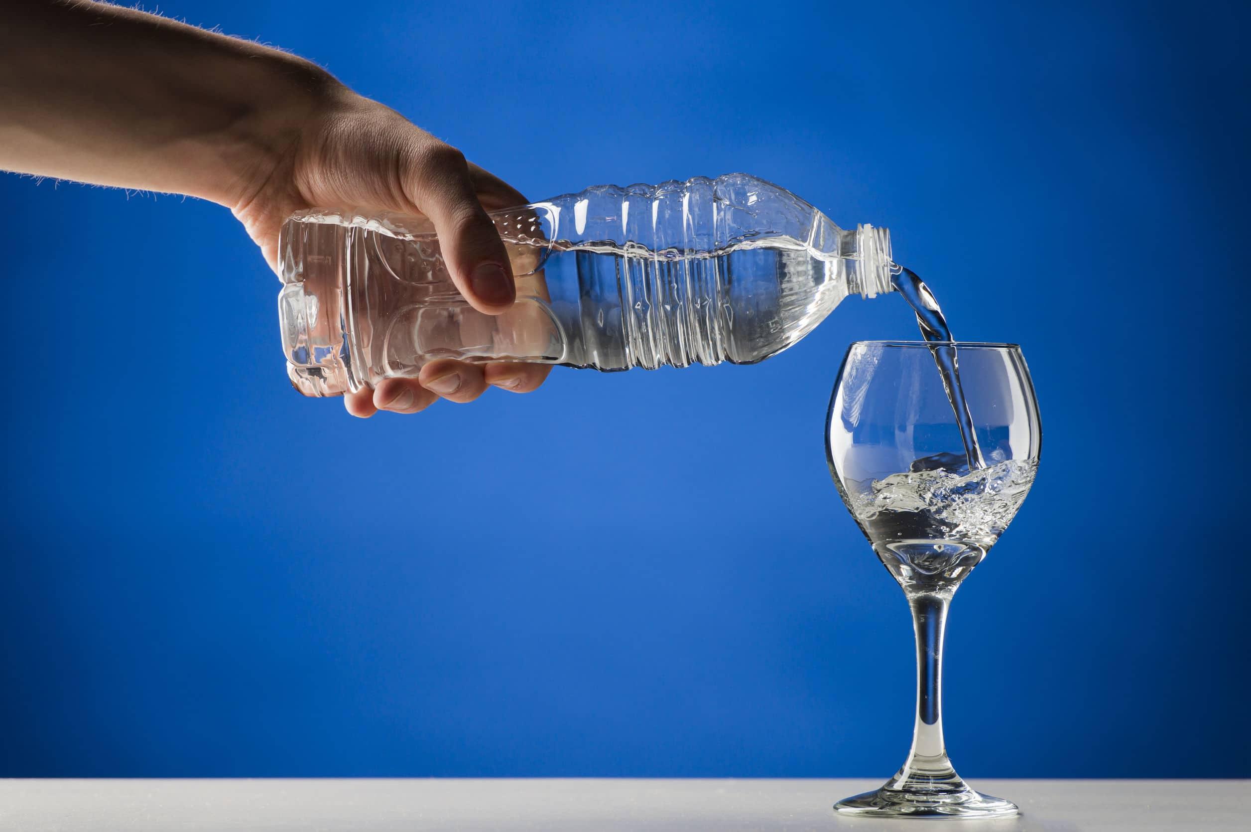 Mão despejando a água de uma garrafa de plástico transparente em uma taça de vidro colocada em cima  de uma mesa com uma parede azul ao fundo.