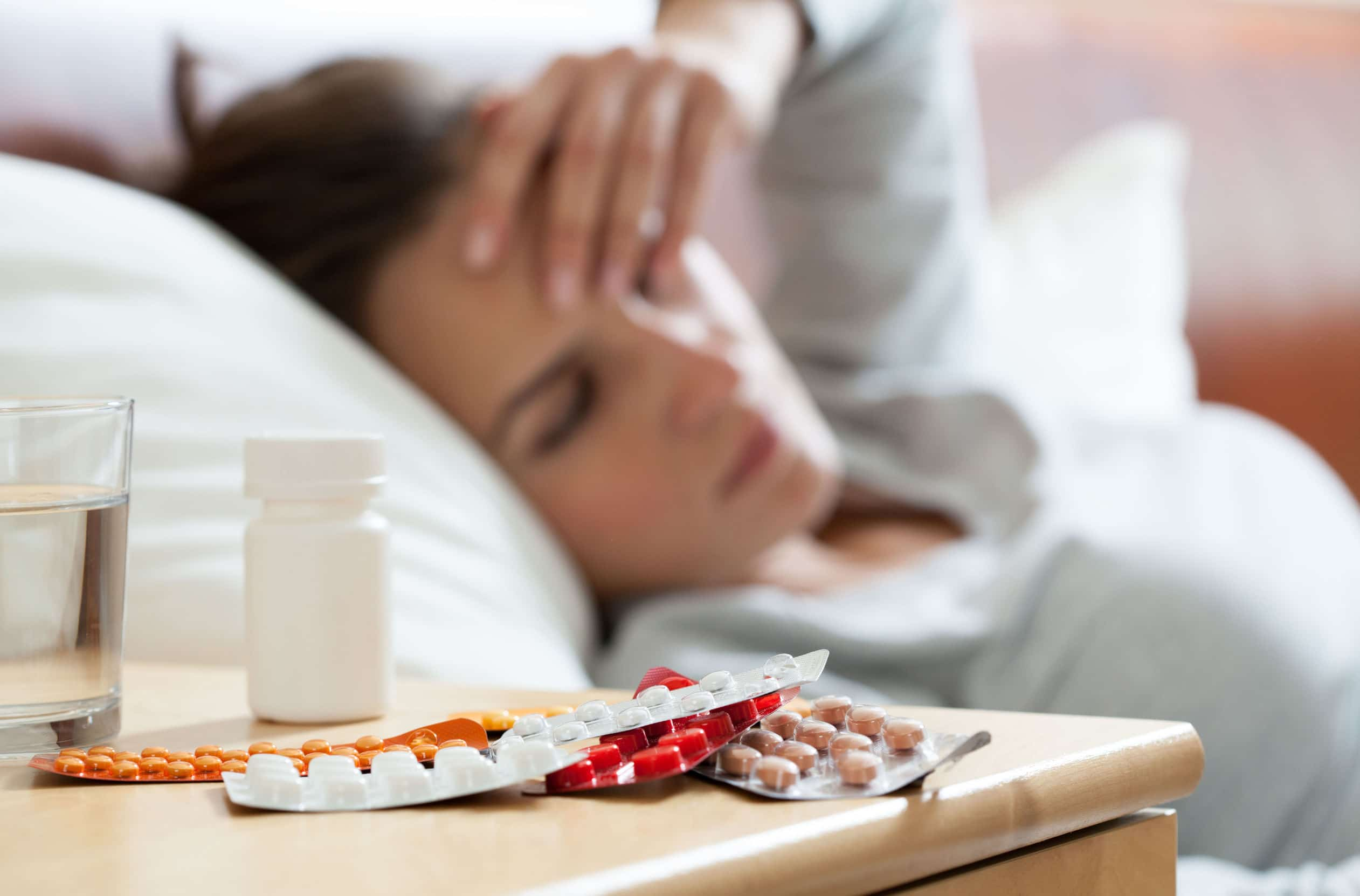 Muitos medicamentos na mesa de cabeceira no quarto com mulher deitada passando mal em cama ao fundo