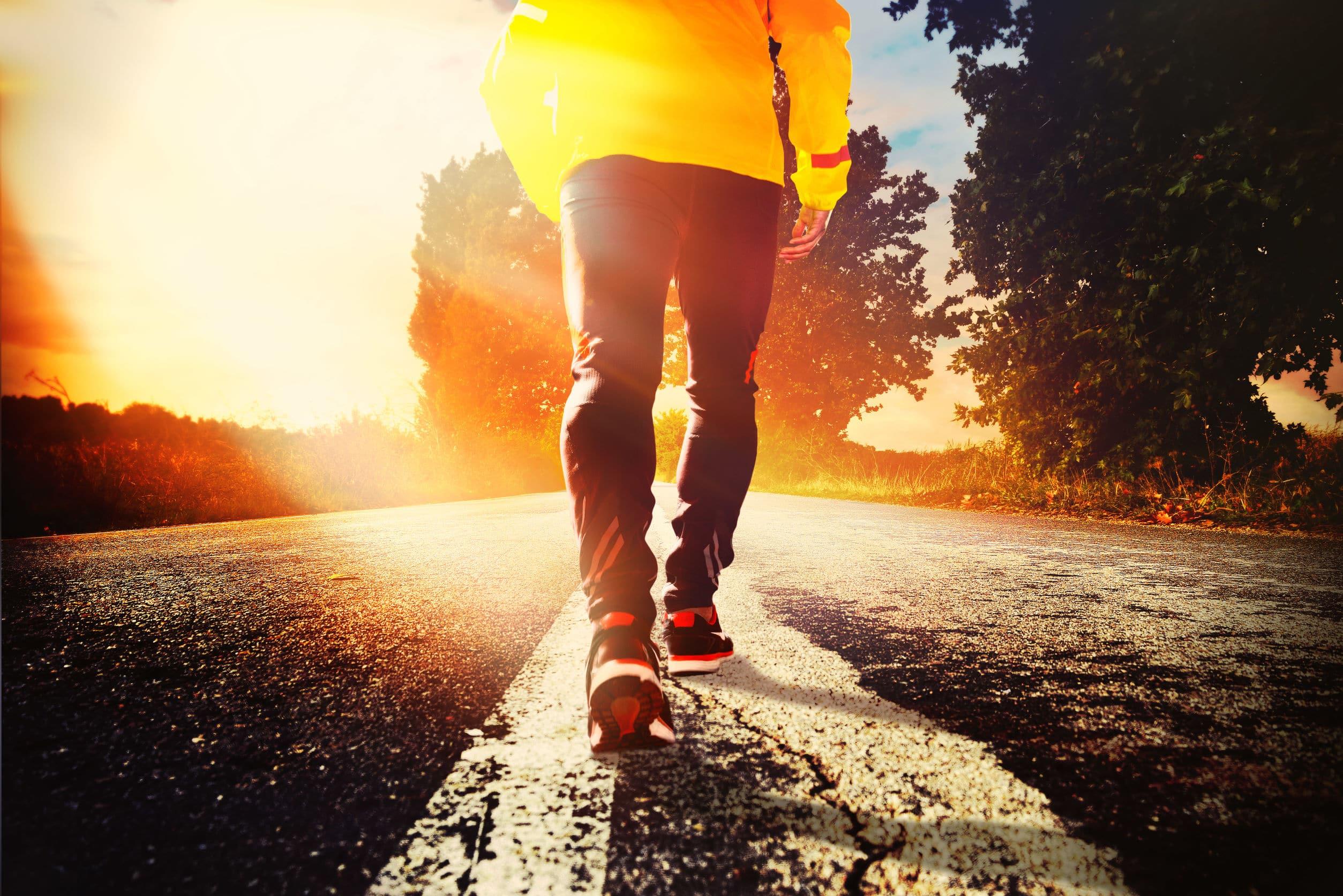 Homem vestindo um casaco amarelo caminhando em estrada perto de árvores na luz do sol.