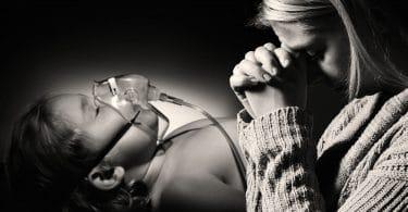 Mulher chorando apoiando o rosto nas mãos ao lado de criança deitada em maca com mascara de oxigênio.