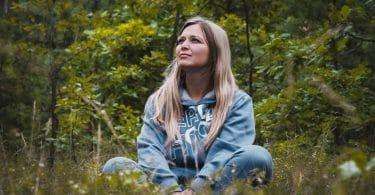 Mulher em pose de meditação sentada na grama.