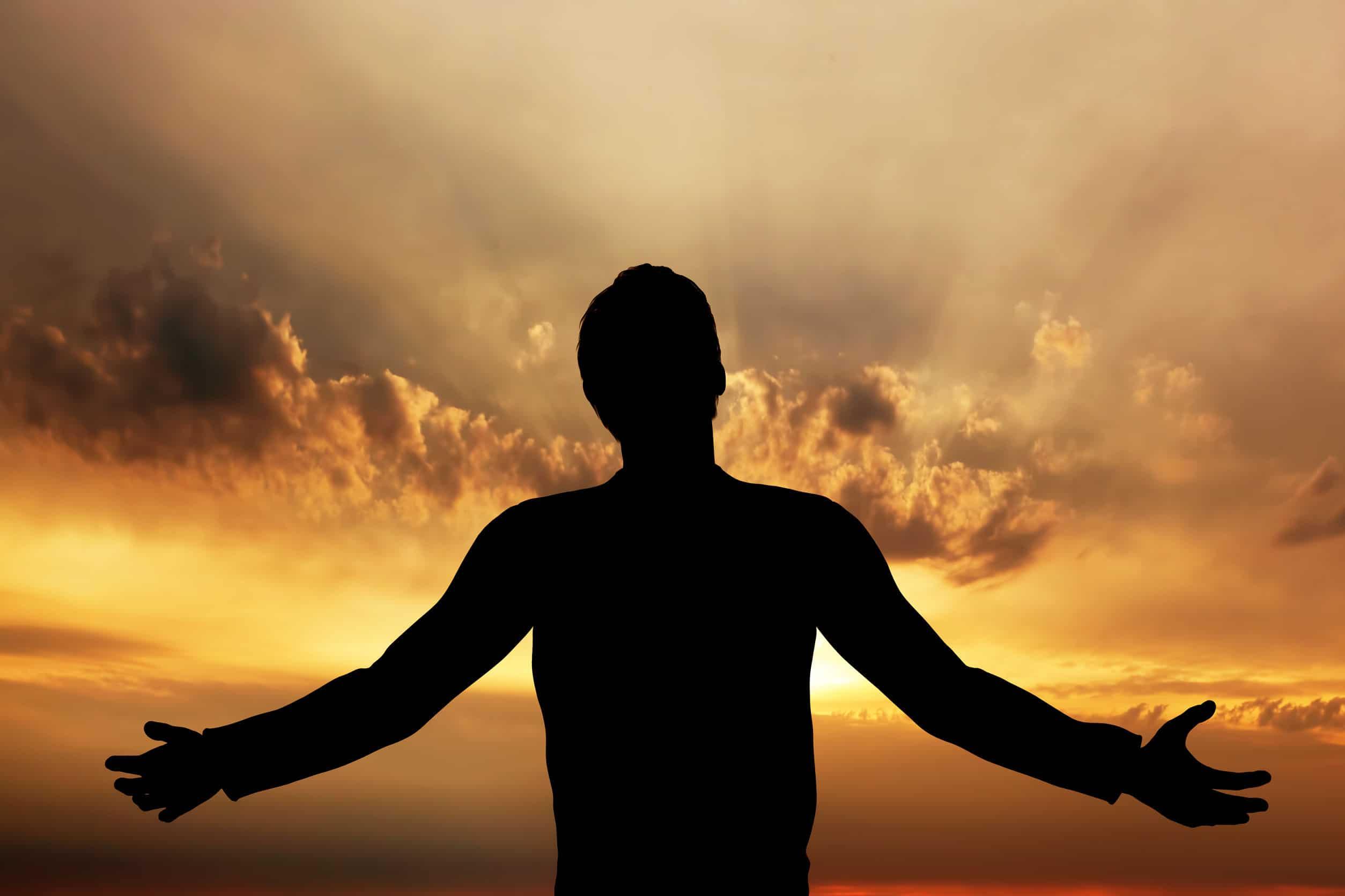 Homem rezando, meditando em harmonia e paz ao pôr do sol.