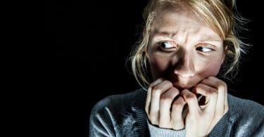 Mulher com medo de algo no escuro.