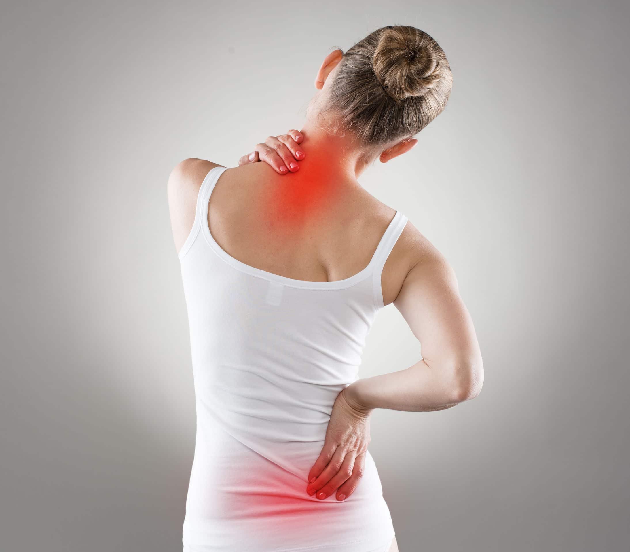 Mulher de costas, apoiando uma de suas mãos no pescoço e outra na sua lombar, demonstrando estar com dor, em frente à um fundo branco.