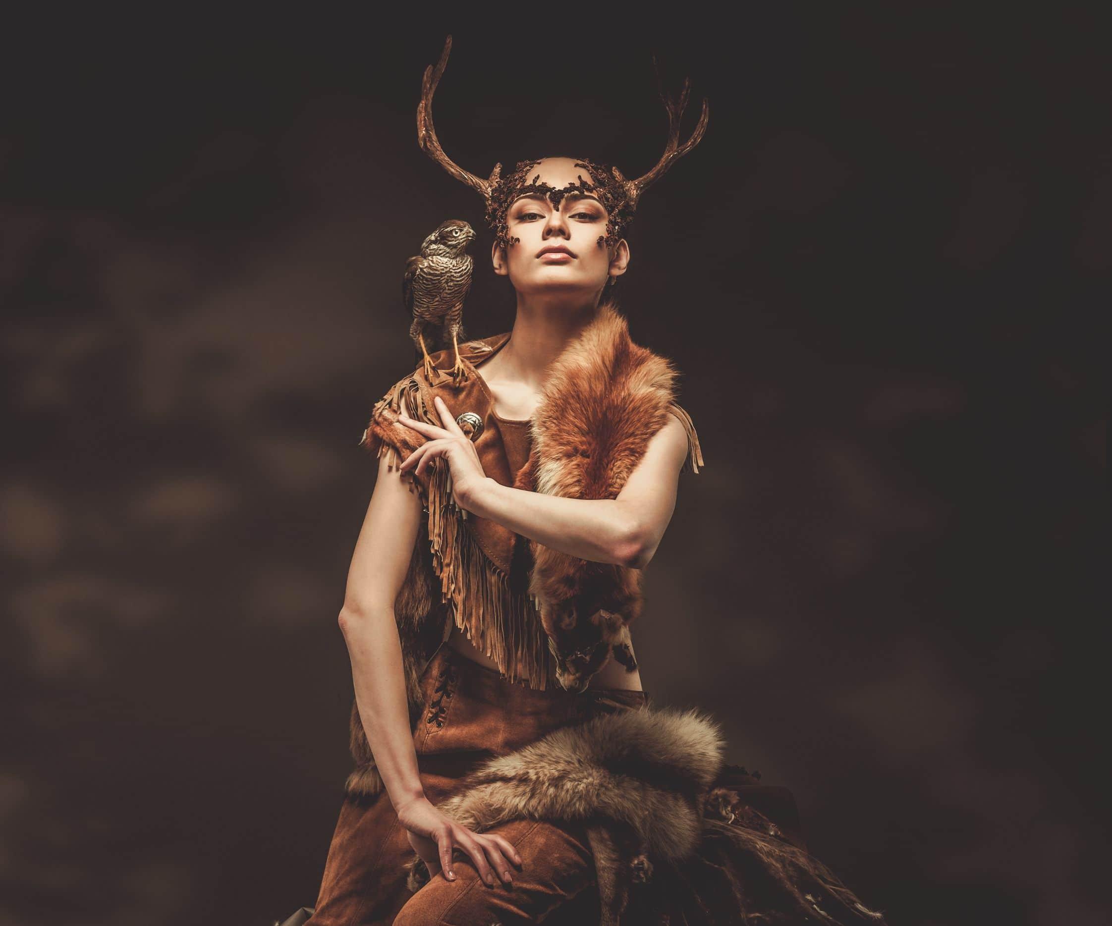 Mulher xamam em vestes de ritual com um falcão no seu ombro