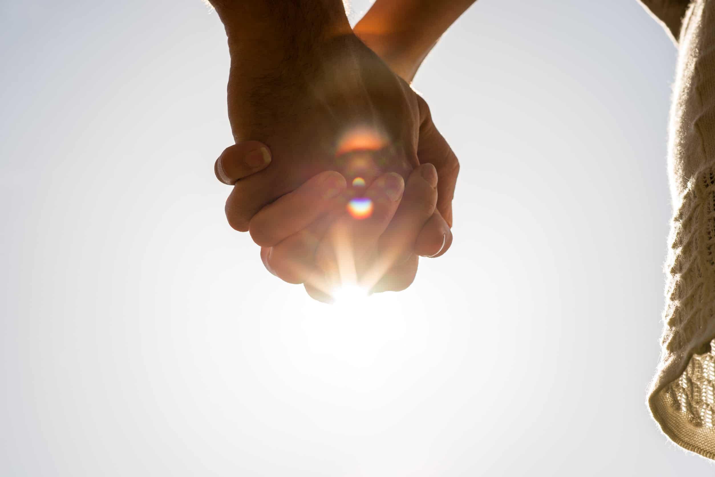 close de um homem e de uma mulher de mãos dadas contra um sol brilhante