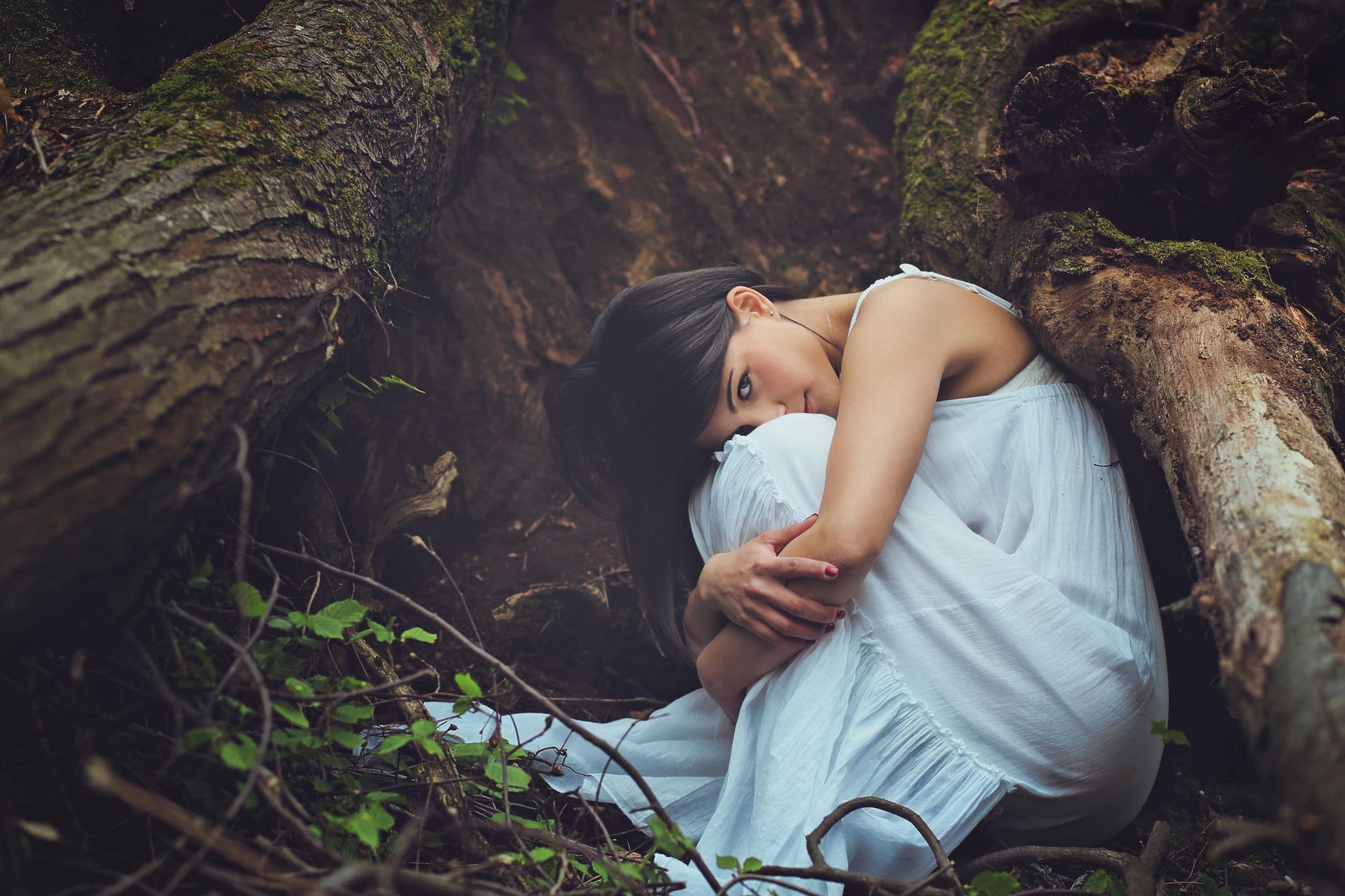 A mulher bonita agachada entre raizes de árvores