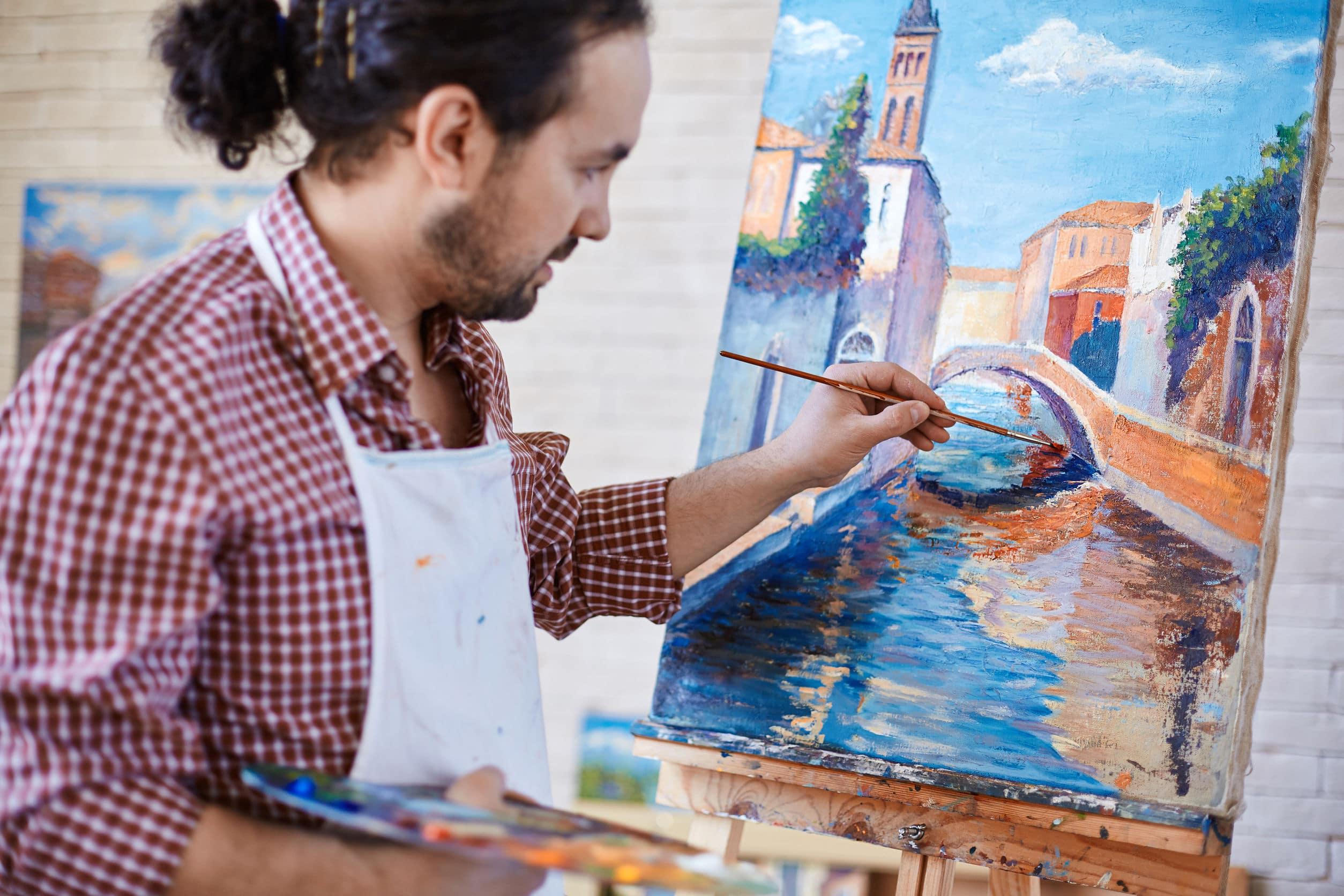 Homem pintando paisagem da itália em um estúdio. Ele usa uma camisa xadrez e tem o cabelo amarrado em um rabo de cavalo.