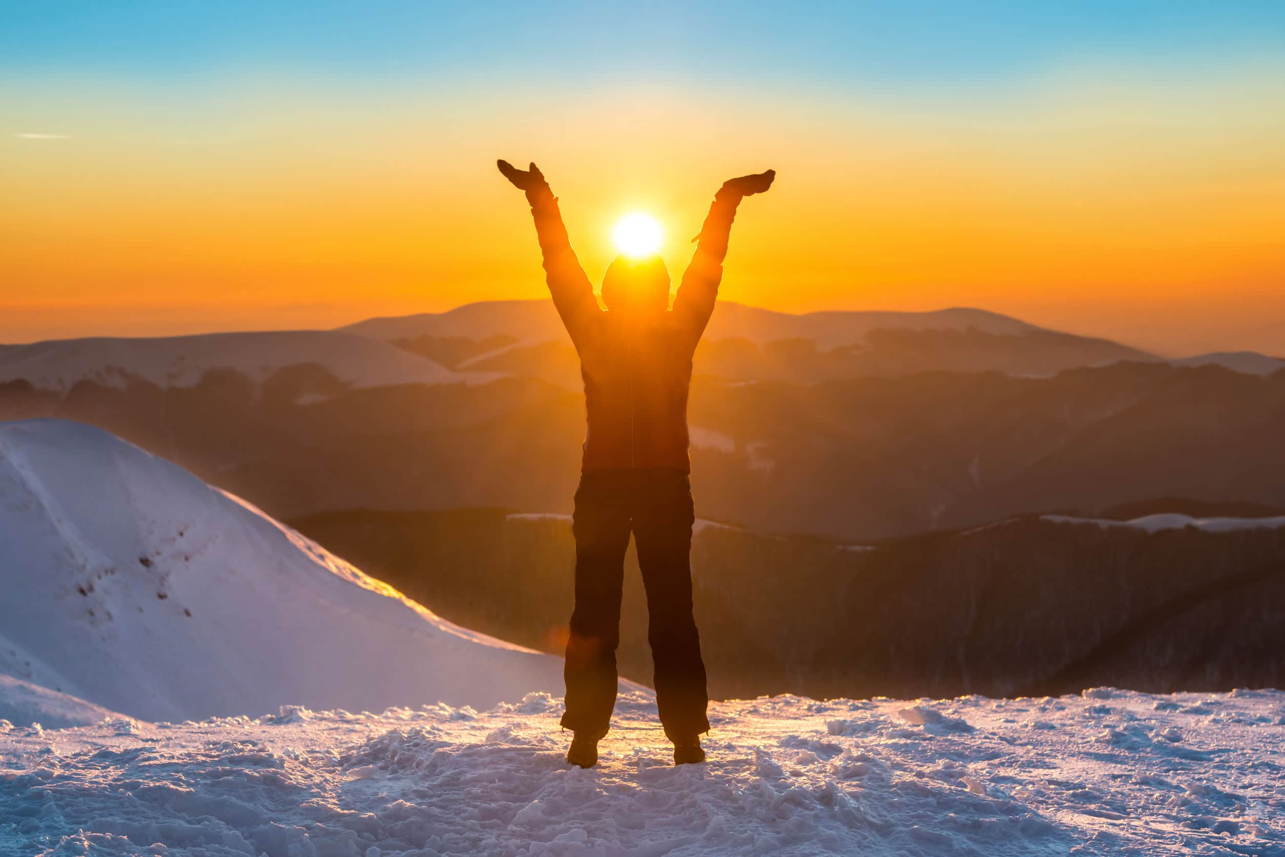 Pessoa no topo de uma montanha com a cabeça posicionada exatamente no lugar onde o sol se poe.