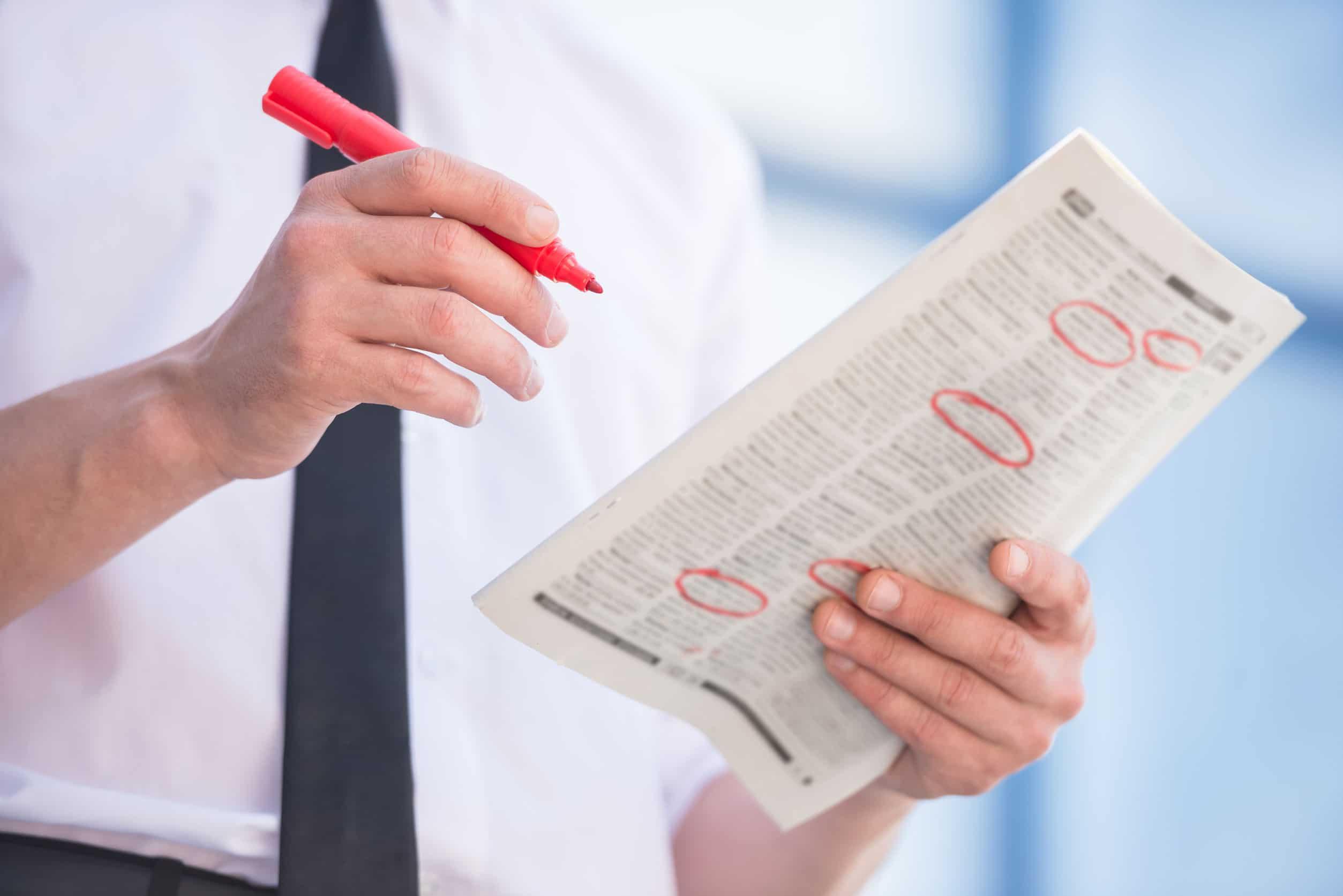 Tronco de um homem com um jornal nas mãos e uma caneta vermelha. Ele circula anúncios de emprego.