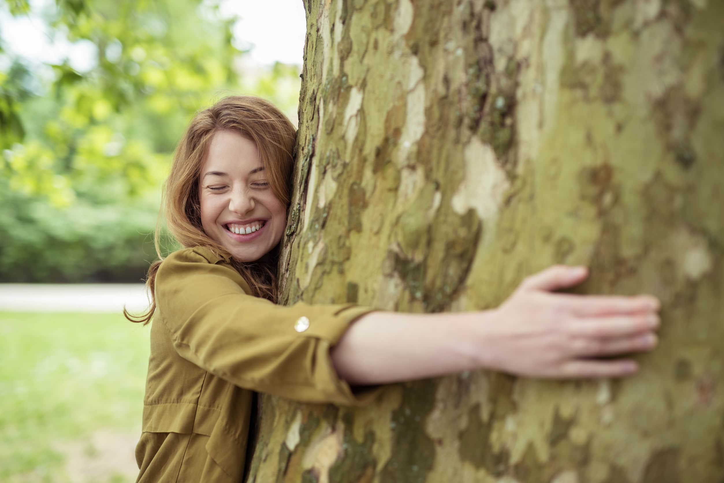 Menina loura adolescente muito feliz abraçando o tronco de árvore enorme em um parque com um sorriso no rosto