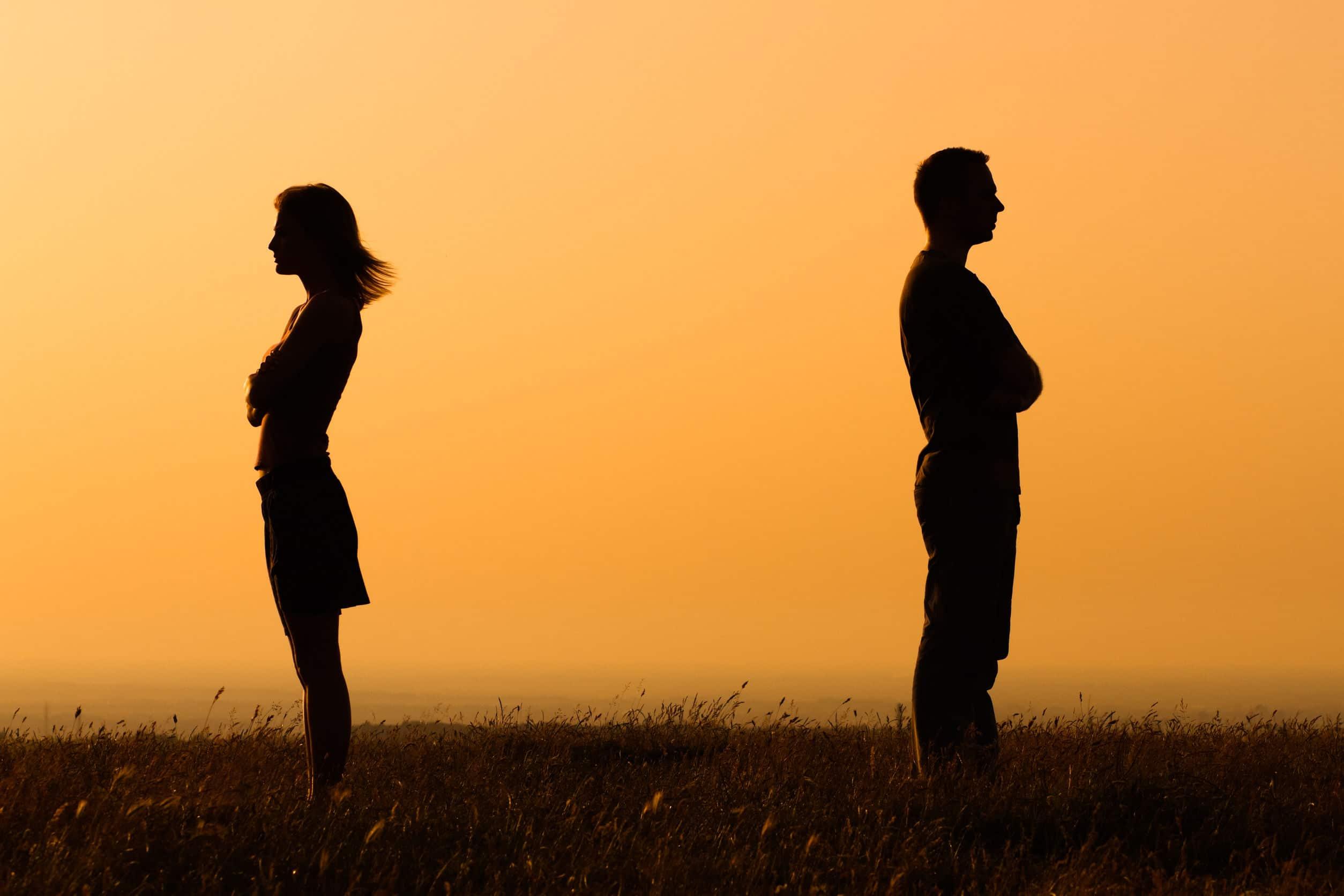Silhueta de homem e mulher, ambos em pé em um campo, um de costas para o outro