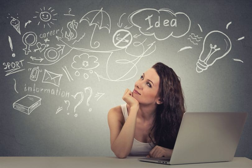 Mulher jovem e feliz sentada em frente ao seu computador pensando.