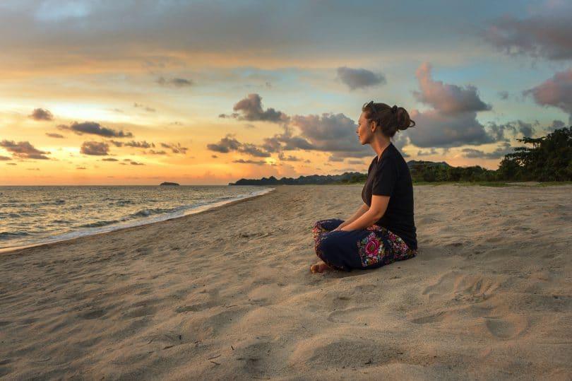 Mulher em posição meditativa sentada na areia.
