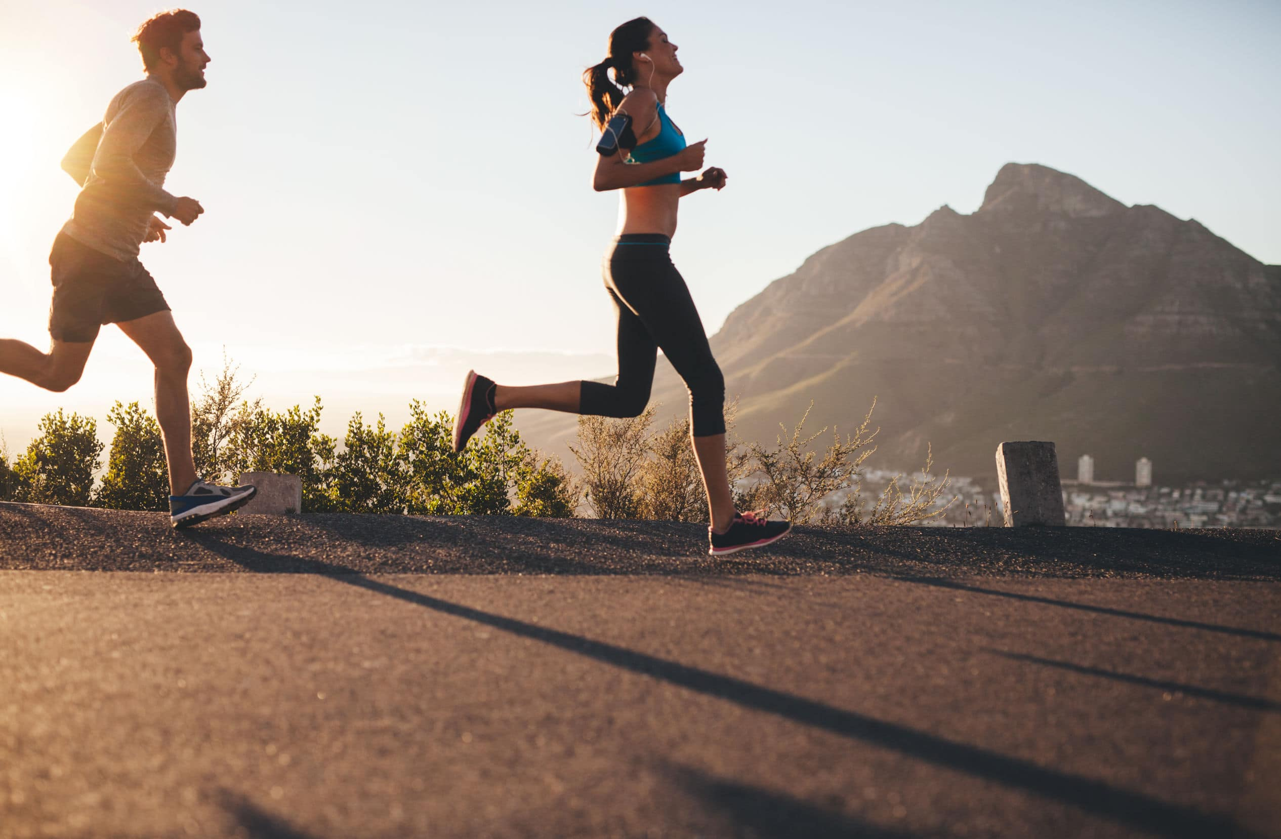 Imagem de uma mulher e um homem correndo. Remete às promessas de cuidar melhor do corpo no ano novo.