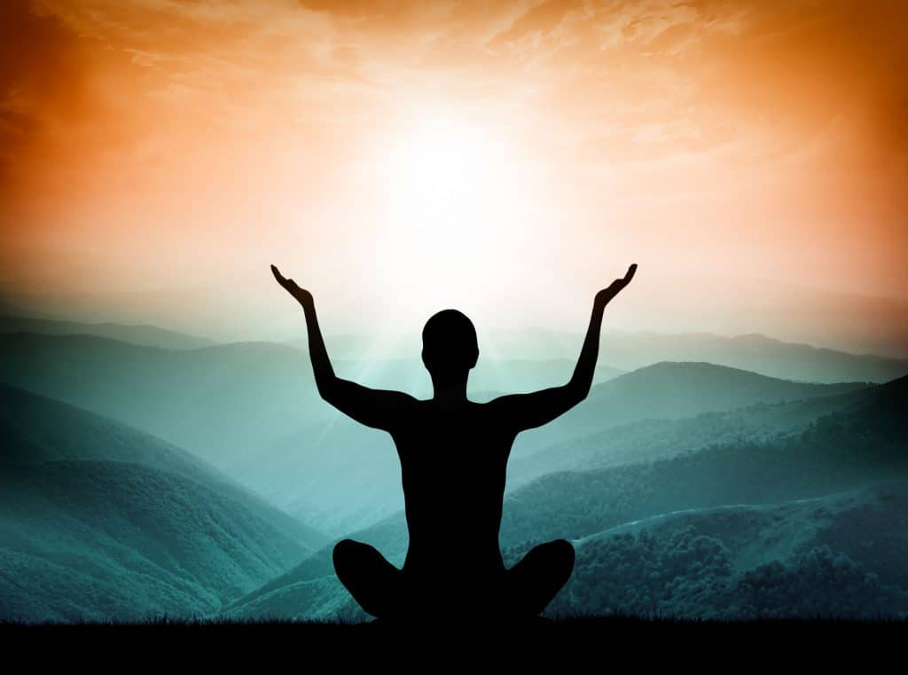 Monje meditando com as mãos para cima.