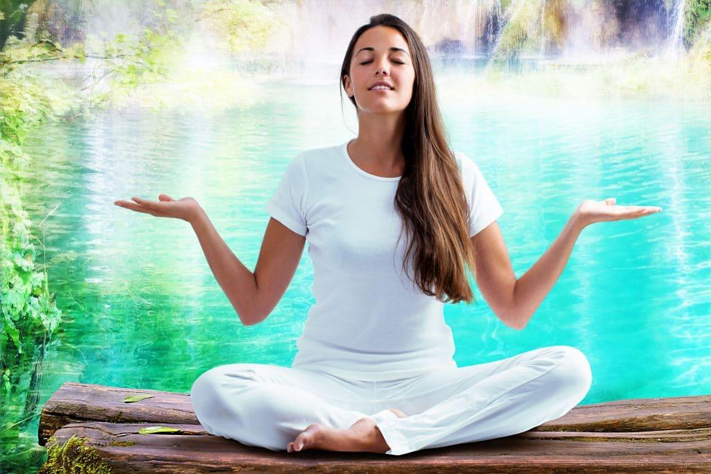 Mulher em posição meditativa com as palmas das mãos voltadas para cima.