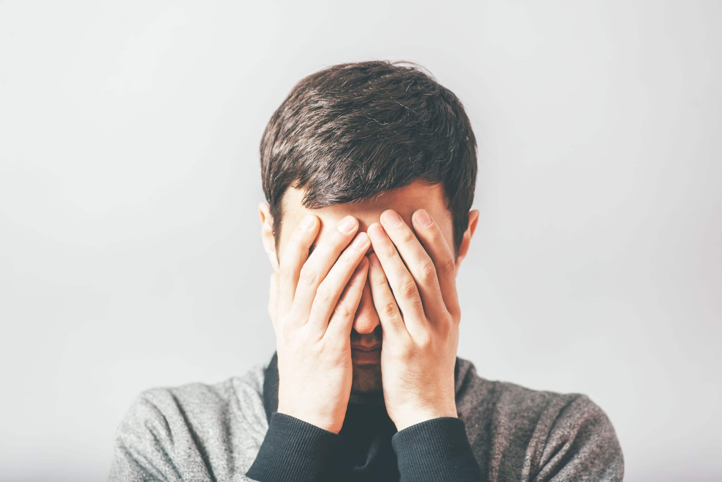 Homem com as mãos cobrindo o rosto em sinal de medo.