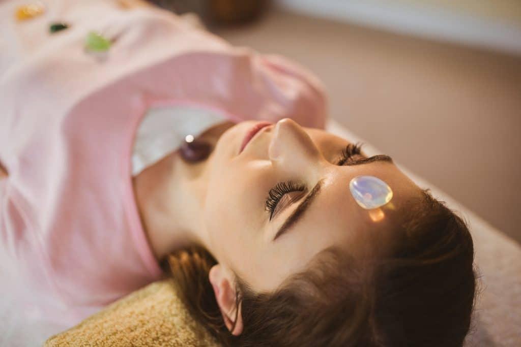 Mulher deitada com cristais em seus chakras.